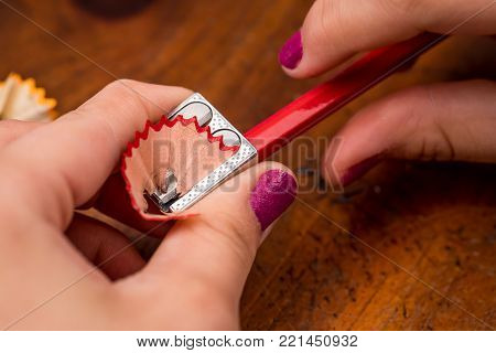 Someone sharpening red pencil with a small pencil sharpener