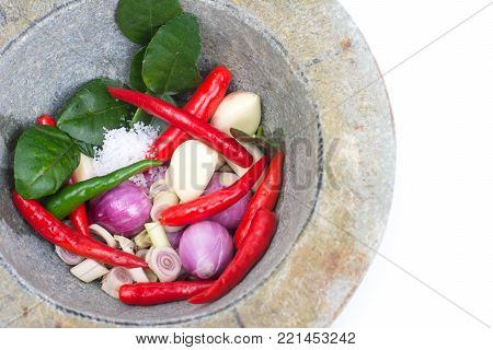 Thai ingredient for spicy paste with garlic, onion, chili, side of granite mortar and pestle on wooden table