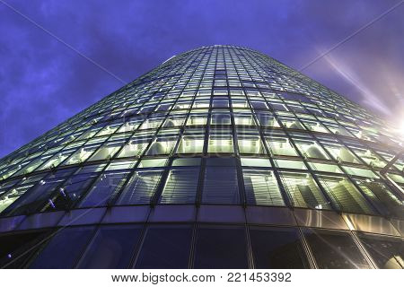 BERLIN, GERMANY - AUGUST 28, 2017; Tower of windows, high-rise modern office building from low angle with diminishing perspective rises into dark night sky.