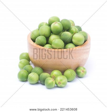 Solanum torvum or turkey berry in wooden bowl isolated on white background