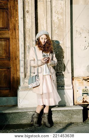 Nice Frenchwoman on the streets of the city. The girl walks around the city. An early walk. A young woman speaks through the phone and sends sms.