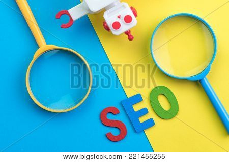 SEO Search engine optimization concept with blue and yellow magnifying glass, alphabet abbreviation SEO and robot on colorful background.