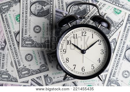 Black alarm clock on US dollar banknotes as time for money awareness concept.