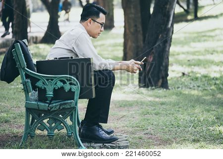 Asian businessman is using a mobile phone, sitting on the bench in the park after work hard.