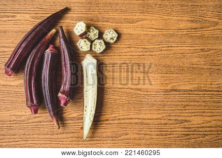 Fresh Red okra on a wooden background.