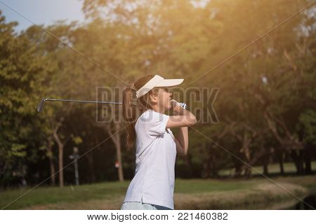 Asian woman golf player swinging driver golf club on golf course.