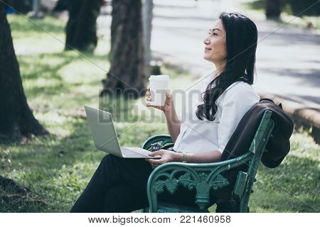 Asian businesswoman working on laptop while sitting on the bench and relaxing with a cup of coffee in a public park.