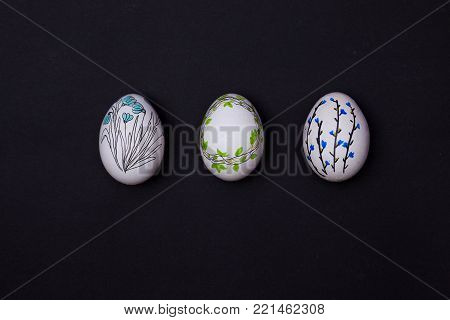Easter eggs painted on black. Top view