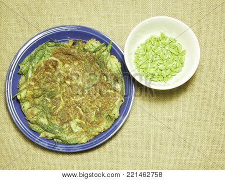 Thai-style omelette with herb on dish and seed White Popinac Hessian sackcloth woven background,consist of eggs,Climbing wattle(CHA-OM)