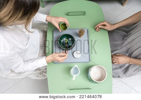 Women preparing a chinese matcha green tea on the green metal table indoors. One girl measures tea powder with a wooden stick over the bowl. On the table there is tea whisk and white jug with water.