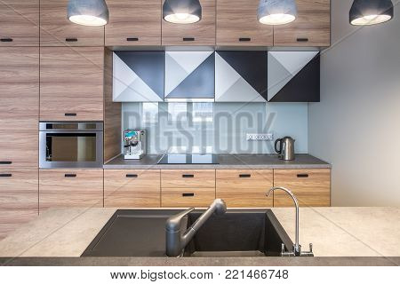 Contemporary kitchen with white walls and luminous lamps. There is a light kitchen island with a sink and two faucets, wooden lockers, oven, stove, chrome kettle, coffee maker. Horizontal.