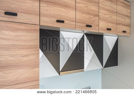 Wooden lockers with black handles on the modern kitchen. There is a kitchen hood and three lockers with geometric black-gray-white prints. Closeup. Horizontal.