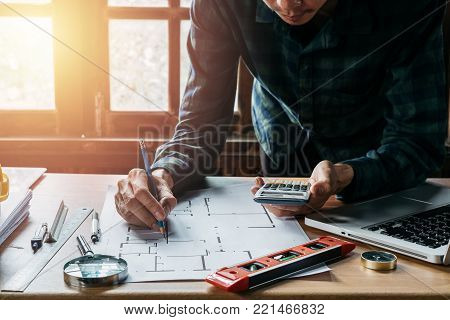 Businessman hand working with laptop and calculator on architectural project at construction site in office.
