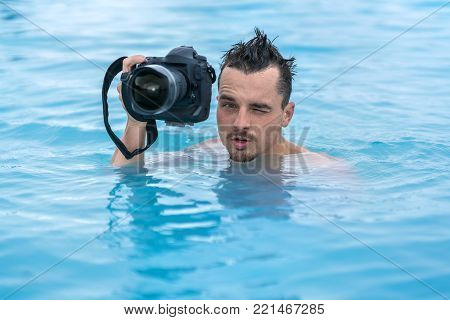 Amusing guy holds a black camera in the geothermal pool outdoors in Iceland. He looks into the camera with a grimace on the face. Closeup. Horizontal.