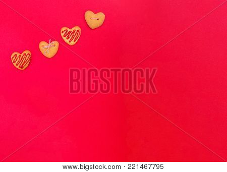 Colorful cookies in heart-shapes on red plate. top view