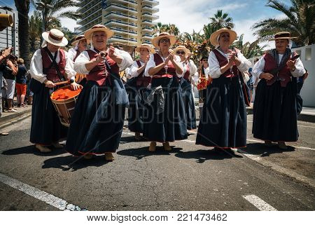 Puerto de la Cruz, Tenerife, Canary Islands - May 30, 2017: Canaries people dressed in traditional clothes walk along the street, sign and play musical instruments. Local residents of Tenerife celebrate the Day of the Canary Islands.