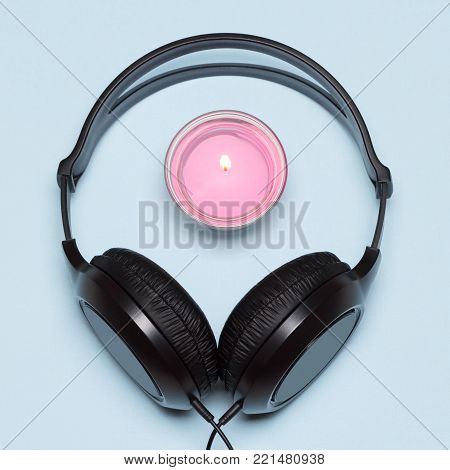 Headphones with burning candle. Meditative and relaxing chill out music concept