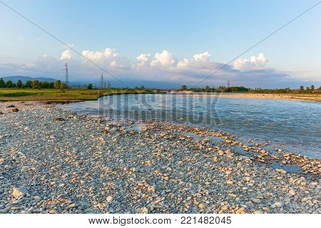 Round white stones lie on the shore of a cold mountain river against a backdrop. mountain river with white stones on the shore..journey to Georgia