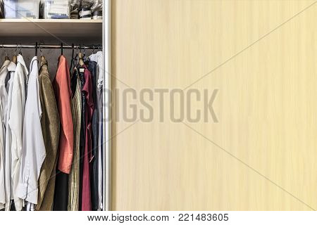 Wardrobe with a shelf, boxes and clothes hanging on the rail. Empty place for an inscription.