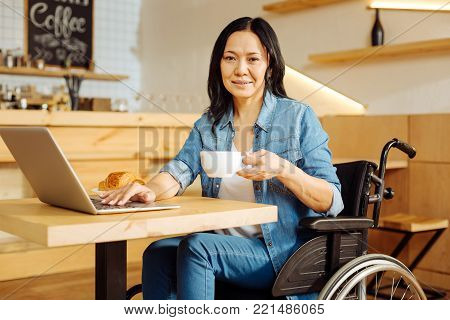 Coffee break. Beautiful happy dark-haired crippled woman sitting in a wheelchair and holding a cup of coffee and working on her laptop