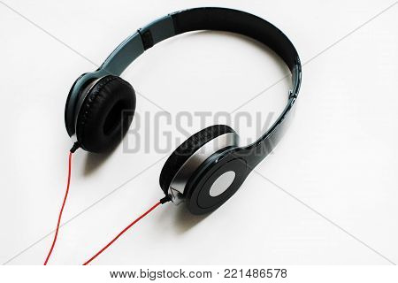 Stereo Headphones Gadget for Music Listening Isolated on White Table Background. Modern Electronic Device with Red Cord. Portable Black Headphones with Empty Copy Space. Technology Music Concept Image