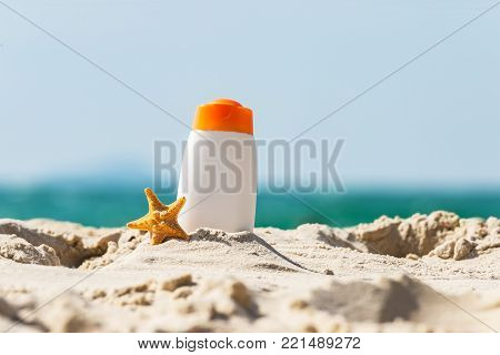 Bottle of sunscreen lotion and starfish on tropical beach, Beach accessories and summer concept, copy space. Summer Concept
