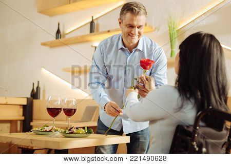 Rose. Handsome content blond man smiling and giving a red flower to his beloved dark-haired disabled woman while having romantic dinner