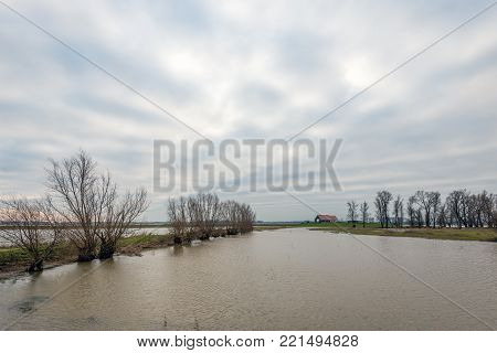 Dutch polder partially flooded by the high water level in the nearby river. In the background is a new farm, built on a mound.