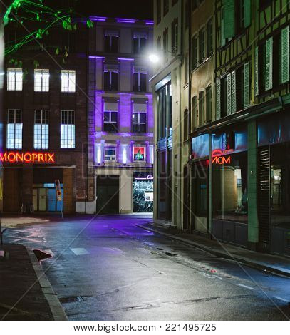 STRASBOURG, FRANCE - DEC 23, 2017: Empty street in France at night with monoprix supermarket store neon logo and Cartier fashion store