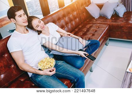 Asian teen couple watching TV together happily. Eating popcorn after he had eaten dinner already in their beautiful home.
