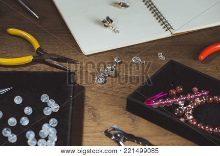 Tools for jewelry making, colorful stone beads. Jewellry workplace.