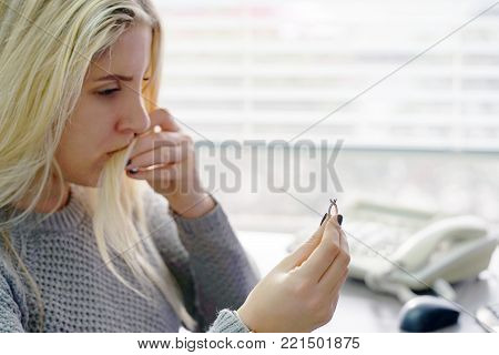 A young blonde woman holding wedding engagement ring in hands, engaged girl doubts about marriage proposal, abandoned wife depressed after getting divorced, help to overcome breaking up, starting new life, close-up