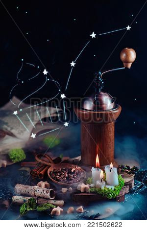 Cupcake constellation in a still life with coffee grinder, coffee beans, star-shaped sugar, and burning candles. Magical still life with open book and copy space. Alternative coffee brewing concept.