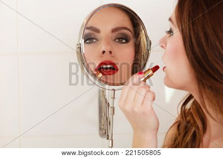 Young girl making makeup in bathroom. Woman take care about look. Looking into a mirror.