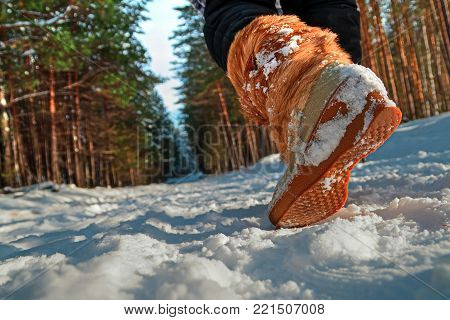 Leg of a woman walking in a winter park. Girl in warm boots walks through the snow. Closeup of winter shoes. Outsole, view from below.