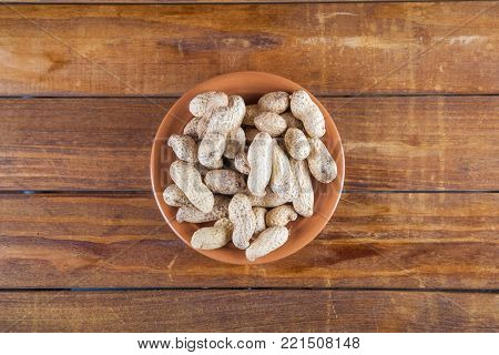 Not peeled peanuts in the plate on wooden background. Top view