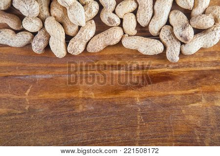 Not peeled peanutson wooden background with copy space. Top view