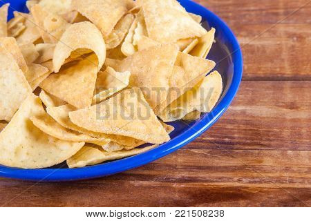 Nachos corn chips in blue plate on wooden table