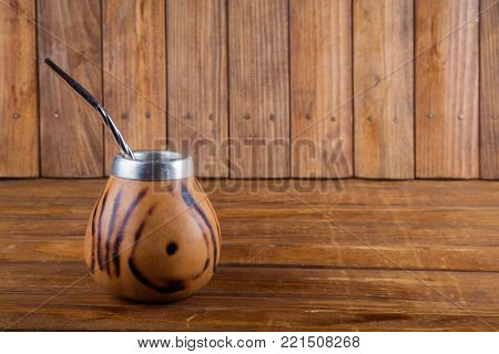 Calabash and bombilla on wooden background with copy space