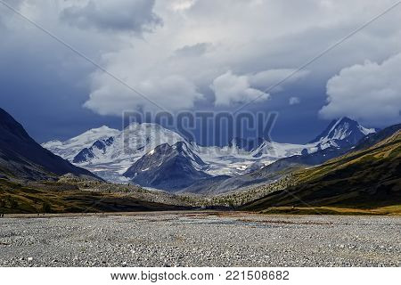 Rocky river valley glacier on the background of dark snow clouds. Big Taldurinsky the glacier. Beautiful view in blue tones.