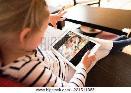 Unrecognizable little girl at home holding a tablet, video chatting with her mother.