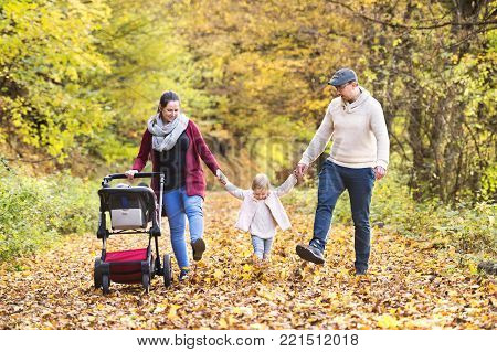 Beautiful young family on a walk in forest. Mother and father with their daughter and son in pushchair outside in colorful autumn nature.