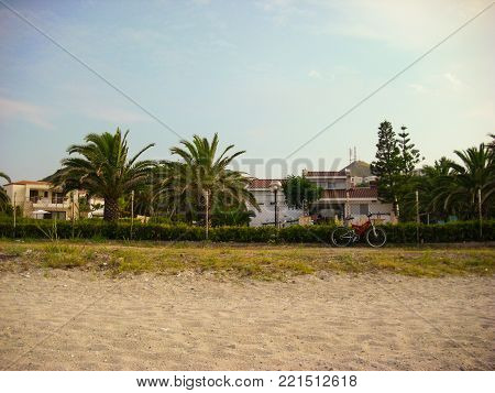 sand beach, palm trees, villas and red bicycle in Halkidiki, Greece.