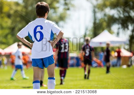 Kid Soccer Player. Young Professional Football Player. Young Boys Kicking Soccer Match
