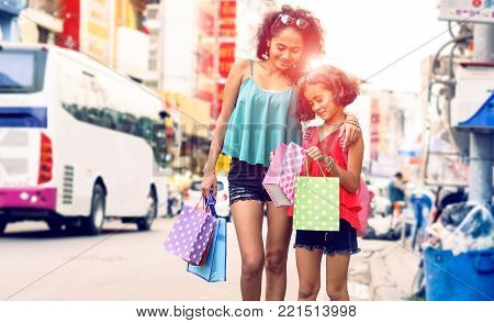 Young mother and daughter shopping together walking on street market at sunset - Beautiful happy asian family holding shoppers looking at present standing in city road - Concept of child happiness