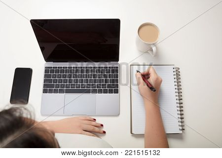 Woman writing a note at a table with a mobile phone and coffee in an overhead view of her hands writing