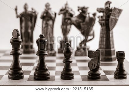 Classic black chess pieces such as king, queen, bishop, knight, rook and the same pieces in the form of medieval figures on the background. Selective focus on classic pieces