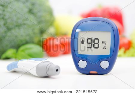 Glucometer and lancelet on vegetables background. Diabetes healthcare concept