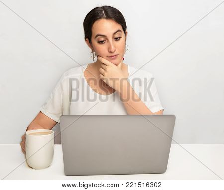Thoughtful young woman working on a laptop computer looking at the screen with raised eyebrows and a sceptical expression