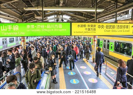 Tokyo, Japan - April 17, 2017: commuters on the sidewalk waiting for the train at rush hour in Shinjuku Station, Tokyo's main station. Yamanote Line loop and Sobu Line local signboard.